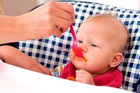 the photo shot of feeding baby food to baby