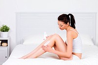 Beautiful young woman caring about her legs with moisturizing lotion _ indoors