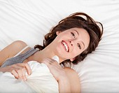 Beautiful and natural young girl on the bed laughing