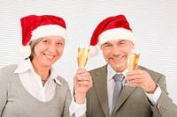 Laughing senior businesspeople wear Christmas Santa hat drink champagne