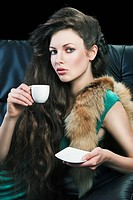 young elegant lady laying down on sofa keeping and drinking from a little cup of coffee. wearing green dress. She looks in to the lens, with right han...