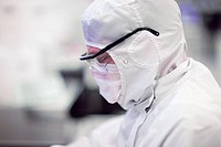 Close up of scientist in clean suit of silicon wafer manufacturing laboratory