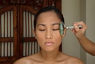Woman receiving facial massage with jade rollers                                                                                                      ...