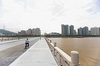 Man riding bicycle on bridge, Shandong province, China