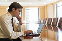 Businessman using laptop in board room