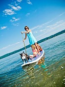 Woman on paddle board with kids and dog