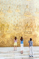 Young tourists looking up at Buddhist bas_relief