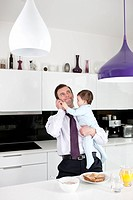 A father trying to use the telephone whilst holding his baby son