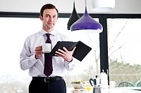 A businessman standing in a kitchen holding a coffee cup digital tablet