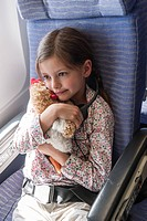 Girl holding stuffed toy on airplane, portrait