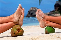 Four sandy feet resting on coconut on tropical beach                                                                                                  ...