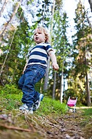 Boy walking through forest