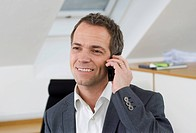 Smiling businessman talking via cell phone