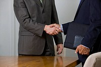 Two businessmen shaking hands in meeting room.