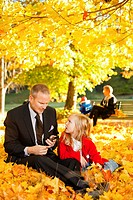 Father and daughter sitting in autumn leaves in park