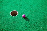 Purple golf ball next to the hole on a mini golf course
