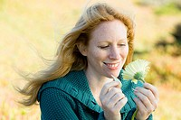 Portrait of a Pretty Redhead Woman Looking at a Flower