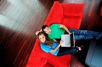 happy young couple have fun and relax at comfort bright apartment and work on laptop computerhappy young couple have fun and relax at comfort bright a...