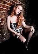Beautiful young woman in sexy lingerie leaning against old brick wall