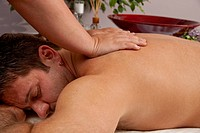 A Caucasian man lies on a massage table getting a massage.