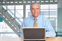 Smiling Businessman at desk in Modern Office Building with Laptop Computer
