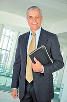 Smiling Businessman in dark suit standing with notebook in office setting