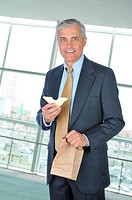 Businessman in office building holding brown bag and sandwich