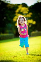 Young excited and smiling girl running in the sunlit grass