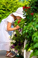 a closeup portrait of a young well_dressed girl smelling flowers in the summer garden