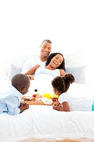Cheerful family having breakfast in the bedroom at home