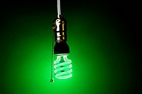 glowing green compact fluorescent bulb hangs from a light socket