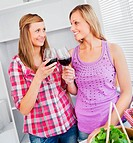 Smiling female friends drinking wine in the kitchen at home