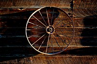 Vintage wagon wheel hanging on weathered wall of an old barn