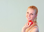 Portrait of an blonde woman with an apple with focus on woman