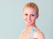 Close_up of a beautiful woman holding a bottle of water looking at the camera with focus on woman
