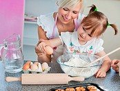 Young mother and child baking cookies in kitchen