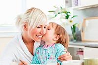 Cute daughter kissing her mother during breakfast in kitchen
