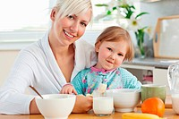 Radiant mother and daughter having breakfast in kitchen