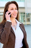 A prettu business woman talking on cell phone at office building