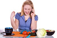 Beautiful Girl in the Kitchen Cutting Tomatoes and Cucumber While Talking on the Phone