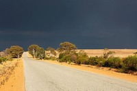 Road with approaching storm over outback landscape, Eneabba, Western Australia, Australia