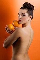 Portrait of young woman holding orange fruit on colored background and with hair stylish