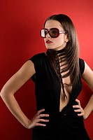 young brunette on red background wearing sunglasses and black dress with a creative hair stylish