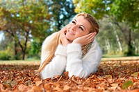 Beautiful young woman relaxing on leaves in the park.