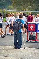 On crutches and unable to participate, a handicapped California middle school student watches a campus physical education class.