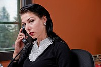 Portrait of a businesswoman sitting with a phone up to her ear. She is looking at the camera with a serious expression. Horizontal format.