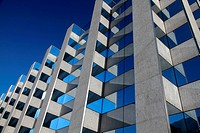 modern symmetrical office building facade with reflecting windows in front of a blue sky