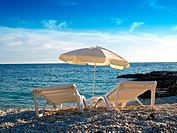 Two deck chairs and parasols on the Adriatic beach.