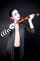 woman mime playing the violin on a black background