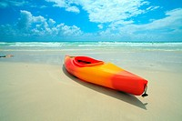 Colorful kayak on the shoreline of South Beach in Miami with blue sky and clouds in the early morning.